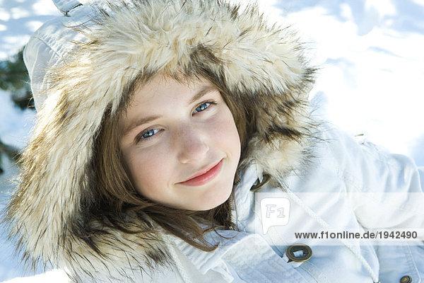 Teenage girl wearing parka in snow  portrait