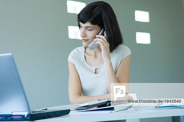 Junge Geschäftsfrau im Büro  mit dem Handy  wegschauen