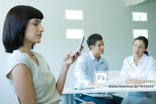 Junge Geschäftsfrau im Büro  Blick auf Handy  Taille hoch  Mitarbeiter im Hintergrund