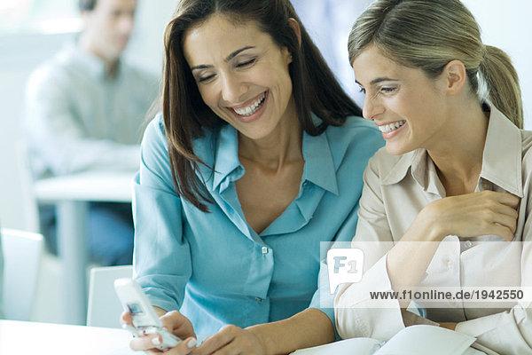 Zwei Geschäftsfrauen  die das Handy anschauen  lächelnd  tailliert