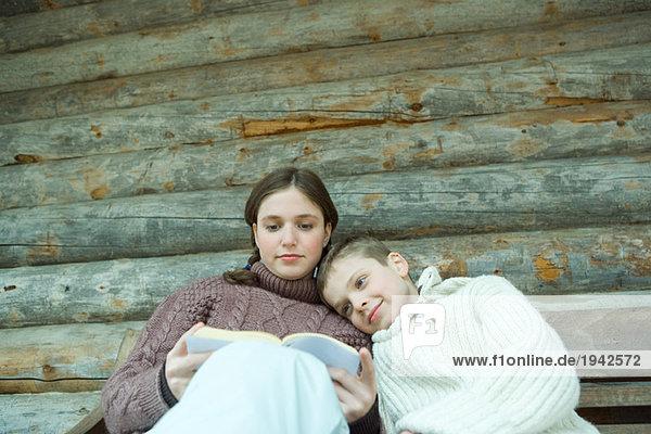 Teenage girl reading book  little brother resting head on her shoulder