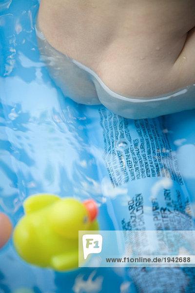 Nacktes Baby sitzend im Planschbecken  Blick auf den Po