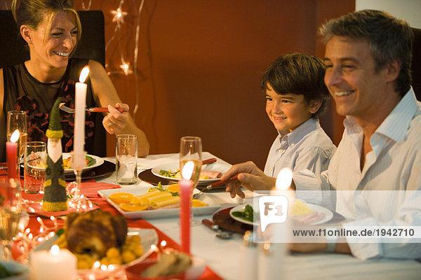 Familie beim Weihnachtsessen  lächelnd