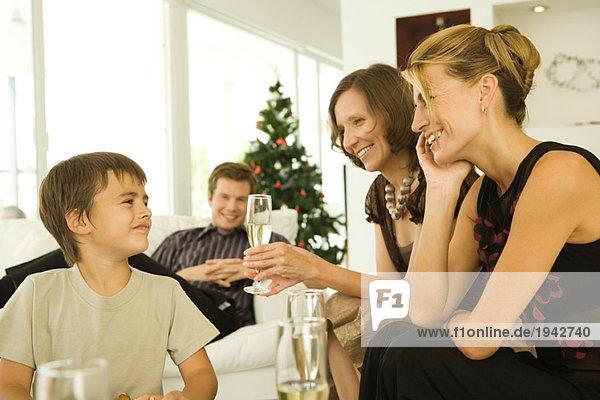Drei Erwachsene trinken Champagner  lächeln den Jungen an  Weihnachtsbaum im Hintergrund