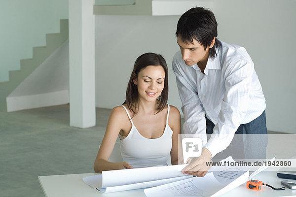 Frau am Tisch sitzend  Blaupausen betrachtend  Mann stehend  über die Schulter schauend
