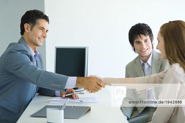 Geschäftsmann beim Händeschütteln mit junger Frau über dem Schreibtisch  männlicher Begleiter der jungen Frau lächelnd