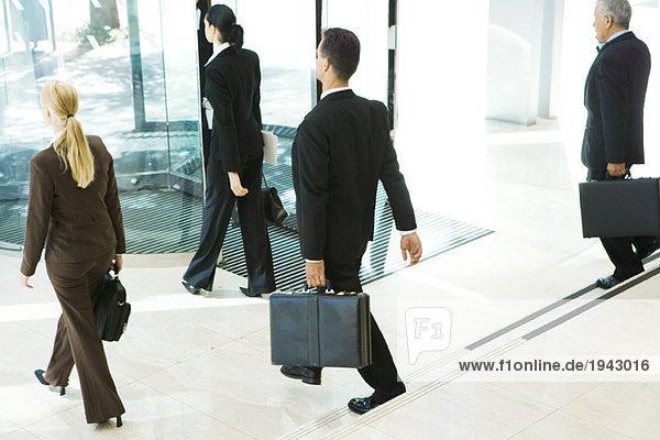 Geschäftspartner mit Aktenkoffern aus der Bürolobby