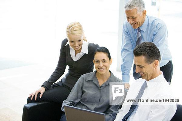 Geschäftsfreunde schauen gemeinsam auf den Laptop  Frau in der Mitte lächelt vor der Kamera