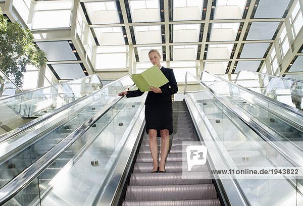 Businesswoman reading on escalator