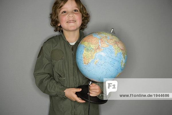 Kleiner Junge in Overall hält Globus
