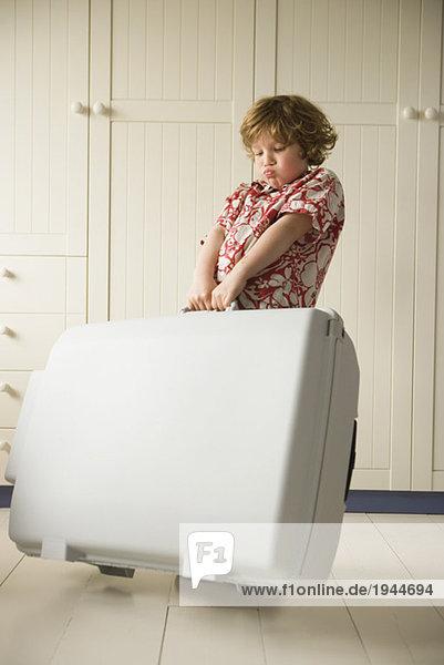 Boy lugging schwere Koffer