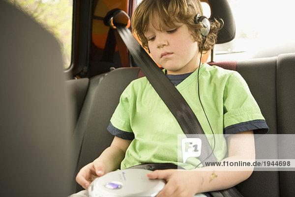 Junge hören Kopfhörer in Rücksitz
