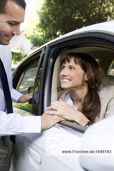 Paar sprechen durch Autofenster