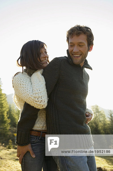 Germany  Bavaria  young couple embracing  smiling