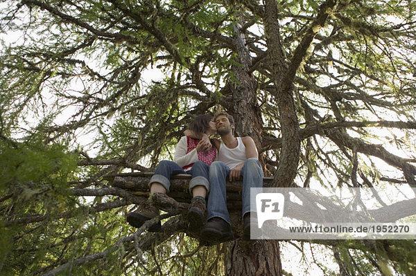 Junges Paar auf Baumhaus sitzend  küssend