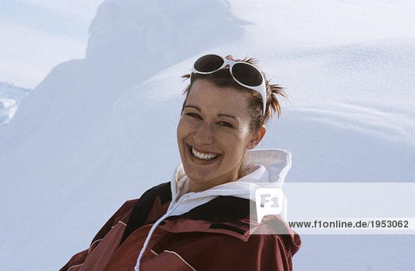 Junge Frau im Schnee sitzend  lächelnd  Nahaufnahme