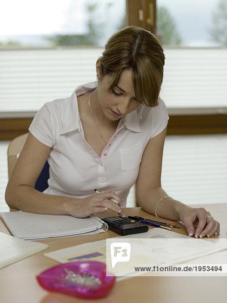 Teenager-Mädchen (16-17) auf dem Schreibtisch sitzend  mit Taschenrechner