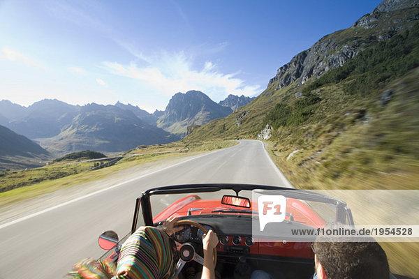 Österreich  Alpen  Paarfahren im Cabriolet  Rückansicht