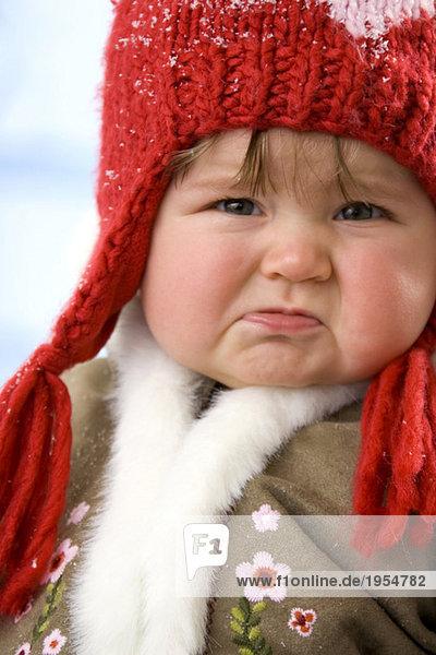 Girl ( 1-2 ) wearing cap  crying  close-up