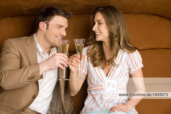 Junges Paar auf dem Sofa mit Champagnergläsern  lächelnd