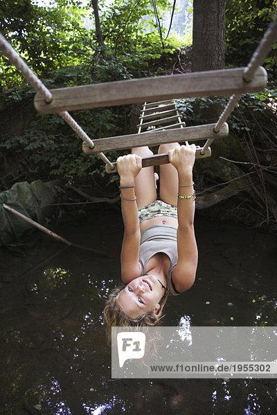 Teenagermädchen (13-15) hängend kopfüber an der Strickleiter