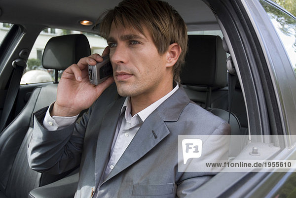 Young man with mobile phone  sitting in car