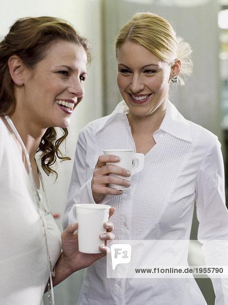 Zwei Frauen mit Pappbechern