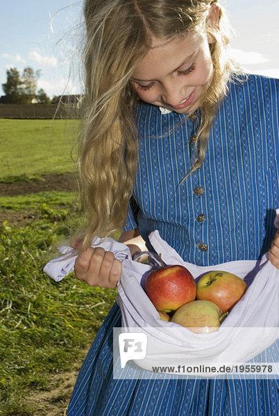 Mädchen (7-9) mit Äpfeln in der Schürze  Nahaufnahme