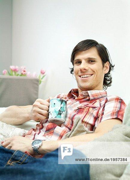 Junger Mann sitzt auf einer Couch mit einer Tasse in der Hand.