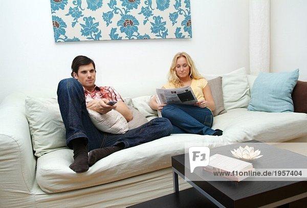 Junges Paar zu Hause in der Couch sitzend