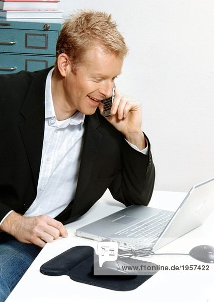 Mann am Telefon am Schreibtisch