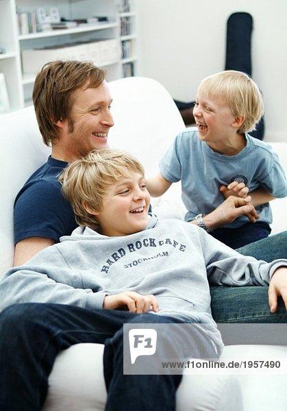 Vater mit Söhnen in der Couch