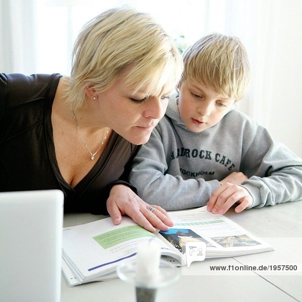 Mother helping her son doing his homework