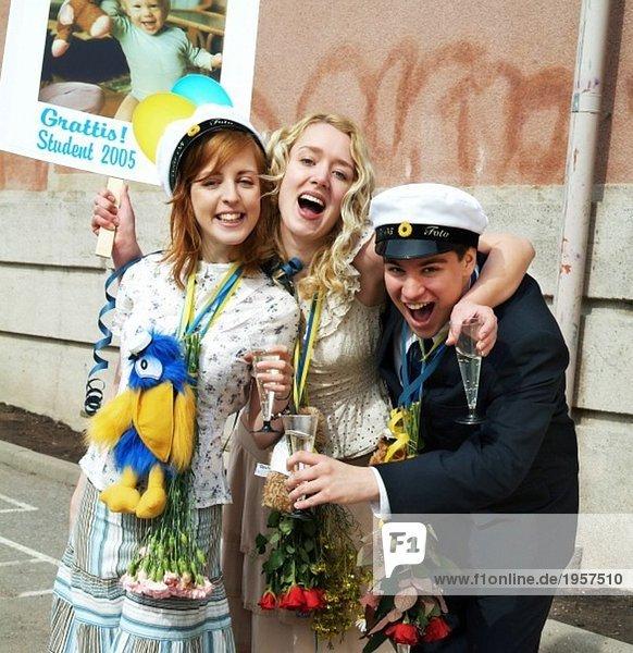 Drei glückliche Teenager  die ihren Abschluss machen.