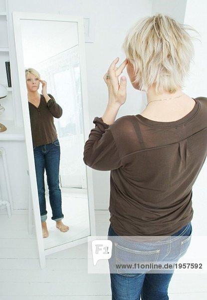 Frau schaut sich selbst im Spiegel an