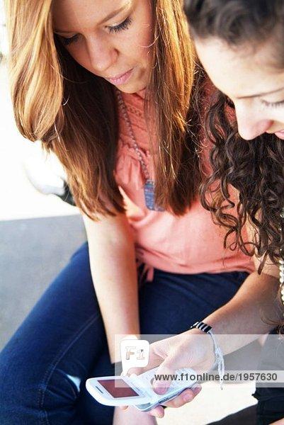 Zwei Mädchen  die auf ein Handy schauen