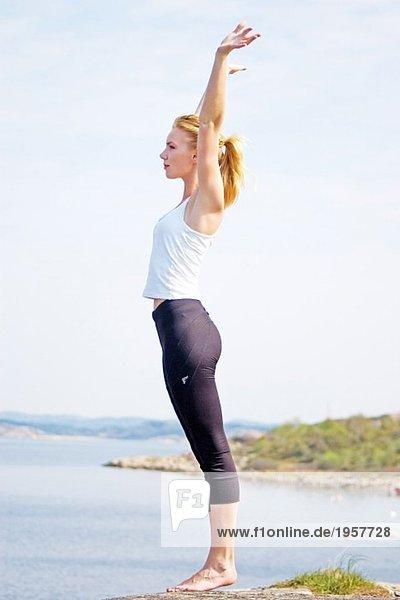 Junge Frau  die sich auf einer Klippe ausstreckt.