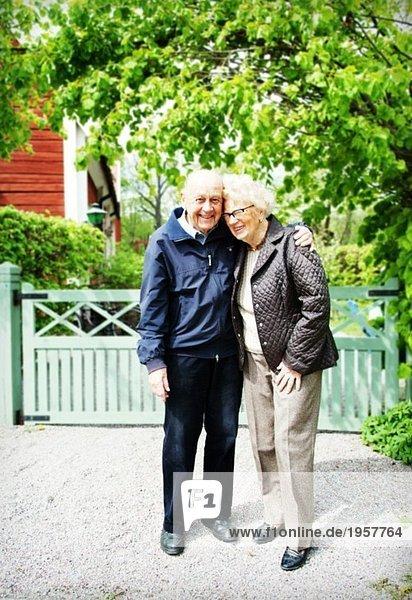 Älteres Paar vor den Toren eines Hauses