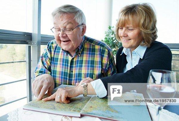 Frau und Mann zeigen in einen Atlas