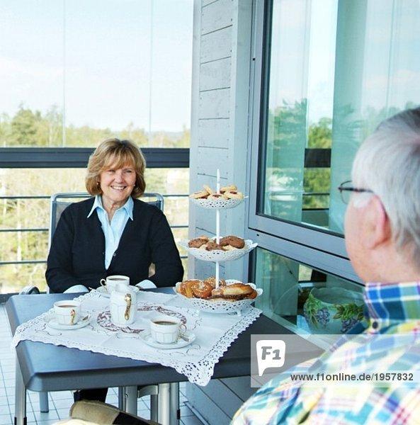 Frau und Mann beim Kaffee auf dem Balkon