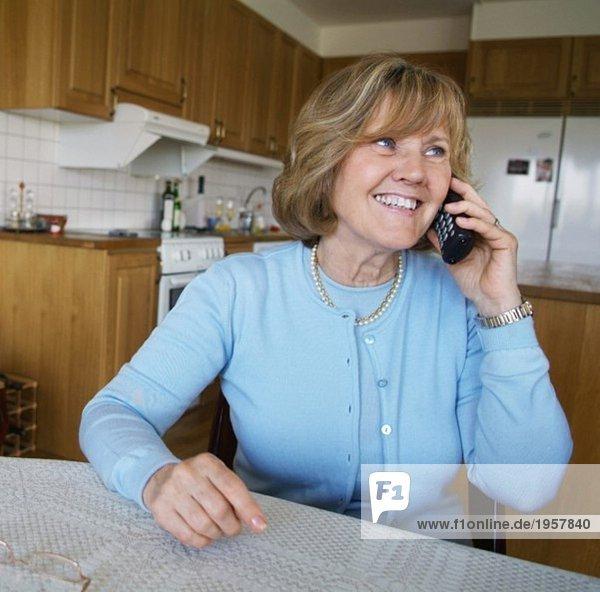 Eine glückliche Frau telefoniert.