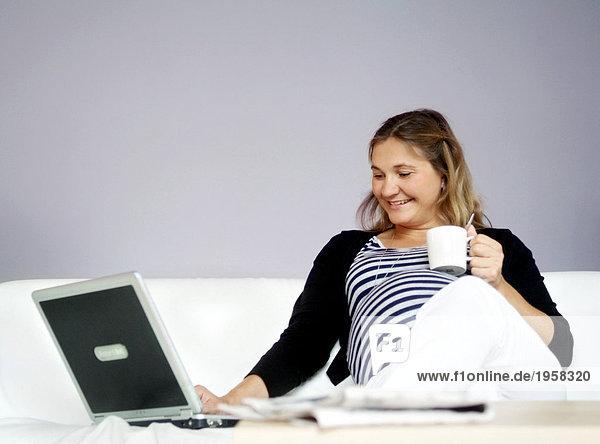 Junge schwangere Frau sitzt in einer Couch mit einem Laptop