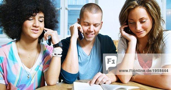 Drei junge Leute sprechen auf dem Handy