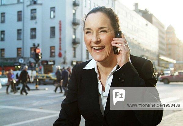 Enthusiastische Geschäftsfrau spricht auf ihrem Handy