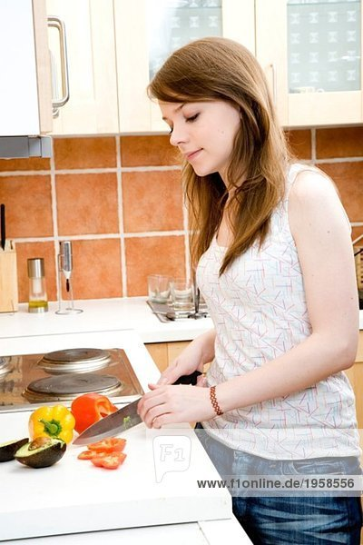 Young woman cutting pepper