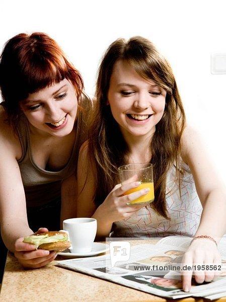 Zwei Mädchen beim Frühstücken und Zeitung lesen