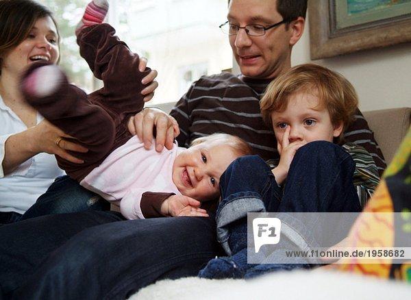 Familie scherzt in der Couch herum