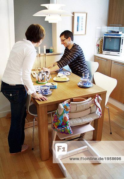 Paar in der Küche an einem gedeckten Tisch