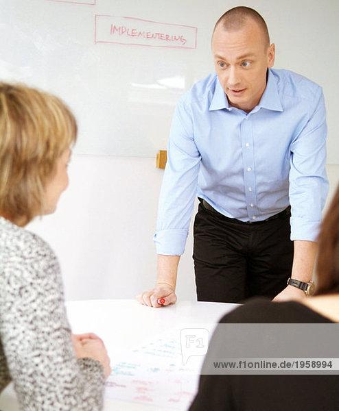 Mann steht an einem Konferenztisch