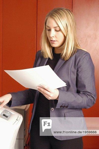 Frau liest Papier am Kopierer